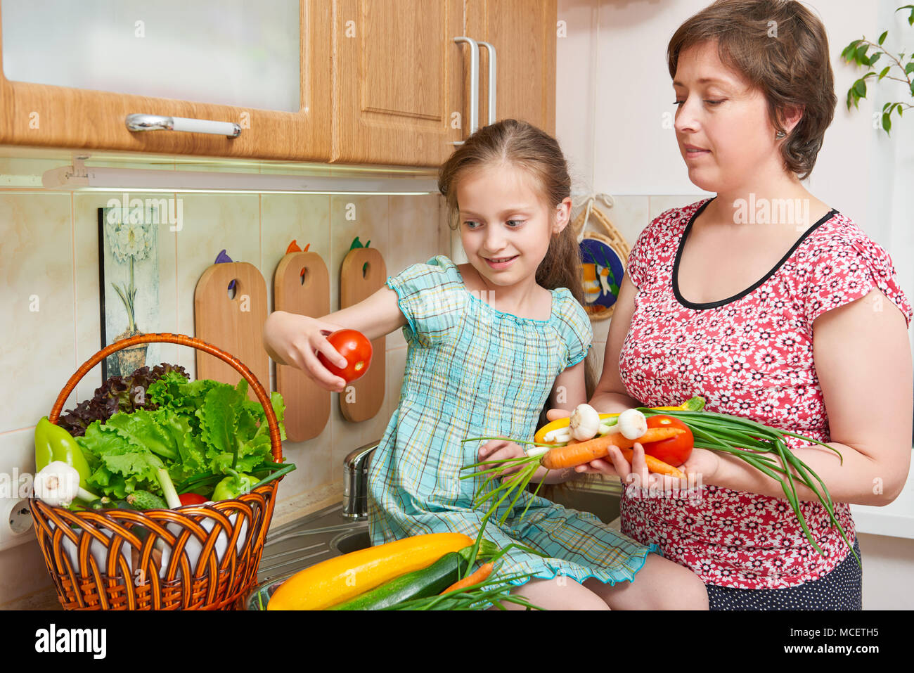 Mother and daughter cooking. Basket of vegetables and fresh fruits