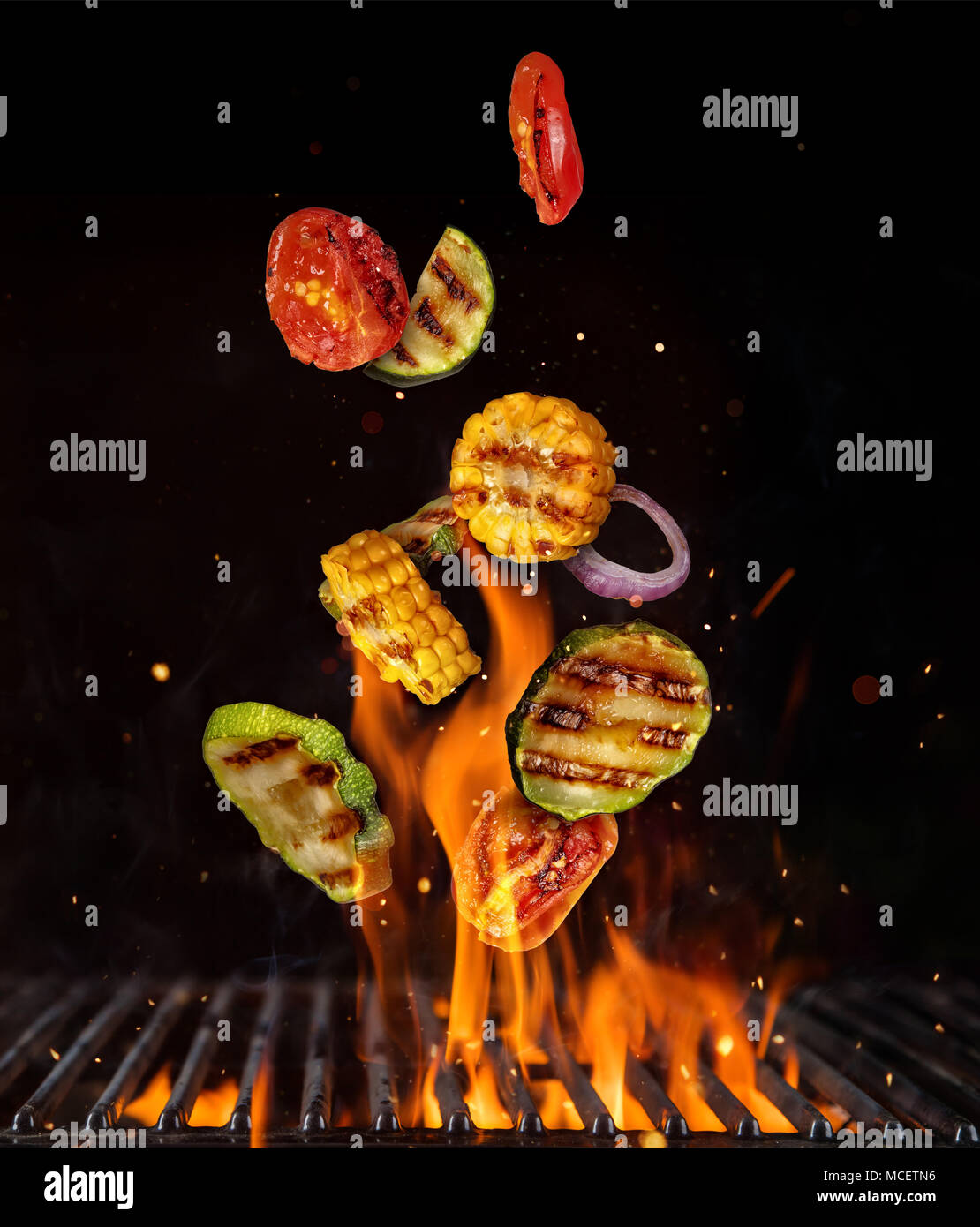 Flying Pieces Of Vegetable From Grill Grid Isolated On Black