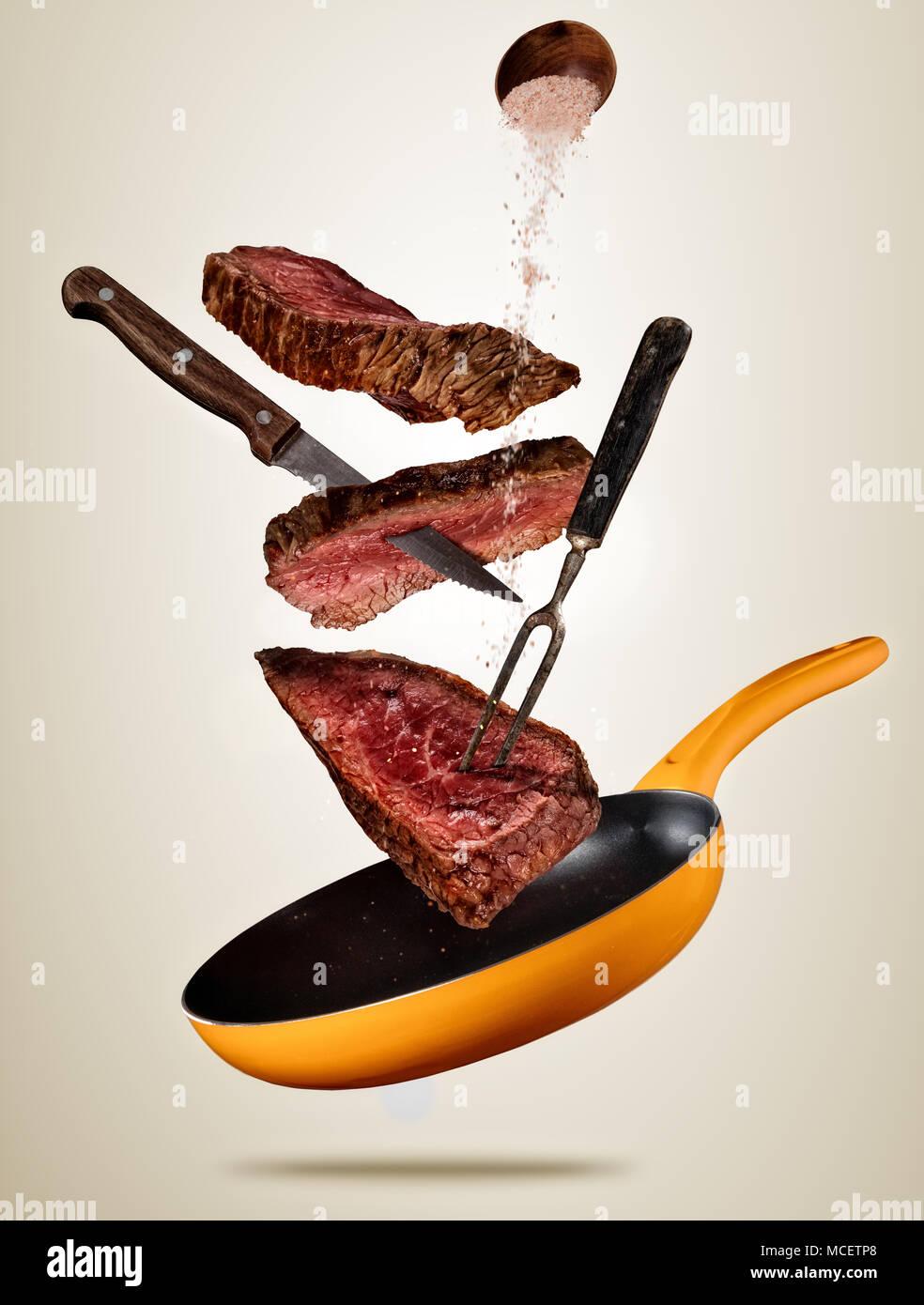 Flying pieces of beef steaks from pan, isolated on colored background. Concept of flying food, very high resolution image Stock Photo