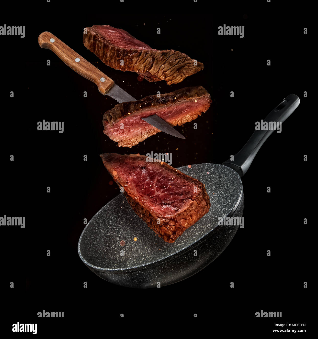Flying Pieces Of Beef Steaks From Pan Isolated On Black Background