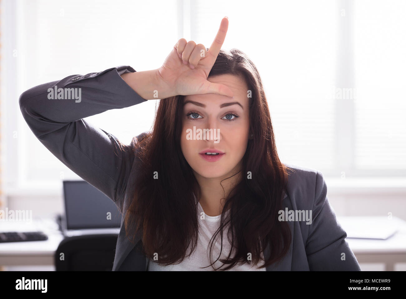 Businesswoman Showing Loser Sign With Fingers On Her Forehead - Stock Image