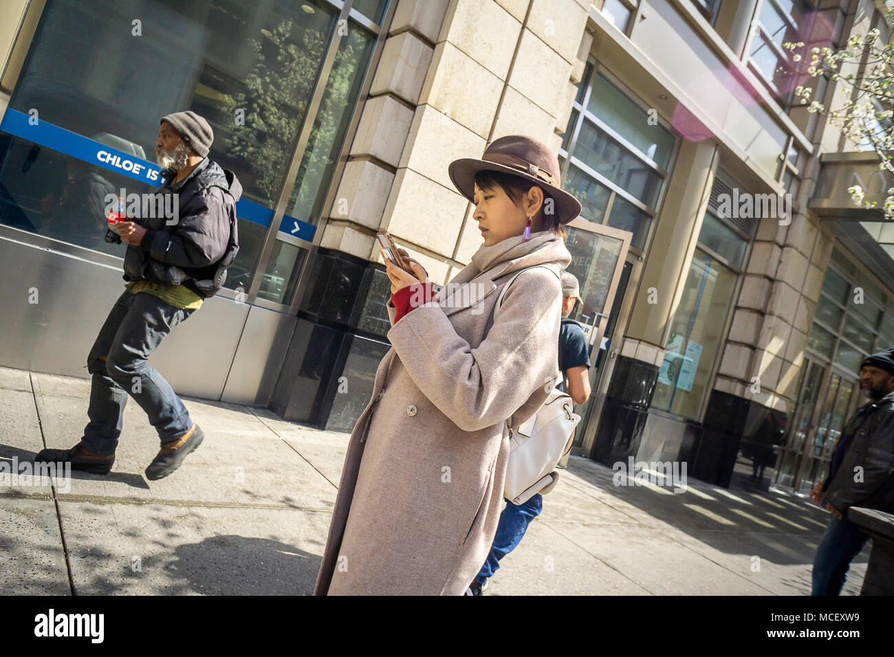 A distracted millennial, engrossed in her smartphone, on Sixth Avenue in New York on Monday, April 16, 2018.  (© Richard B. Levine) - Stock Image