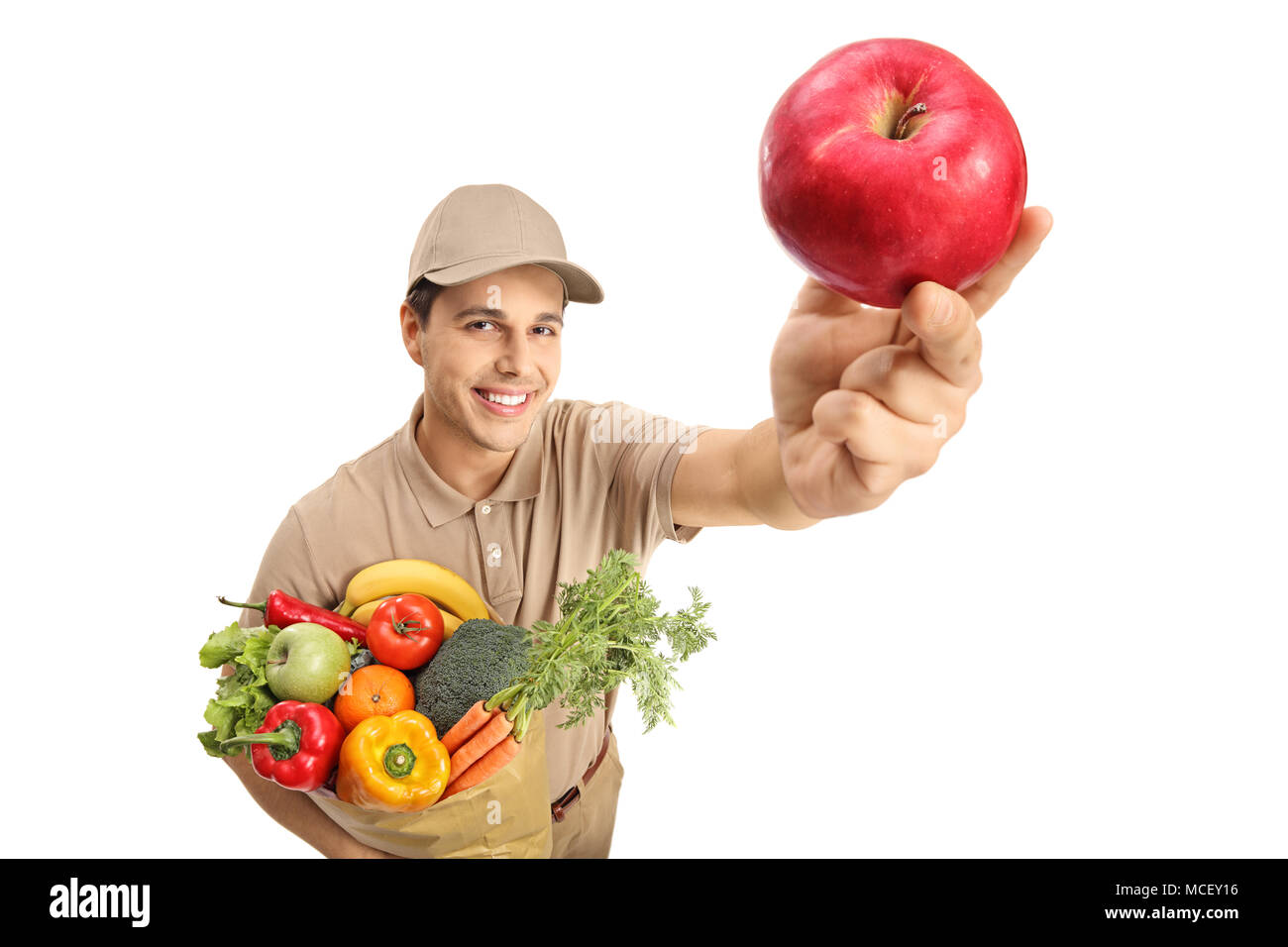 Delivery man with a bag of groceries and an apple isolated on white background - Stock Image