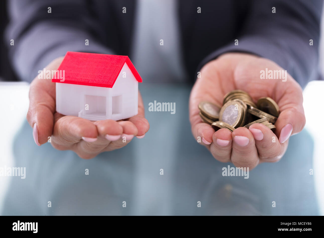 Close-up Of A Businessperson's Hand Holding Coins And House Model - Stock Image