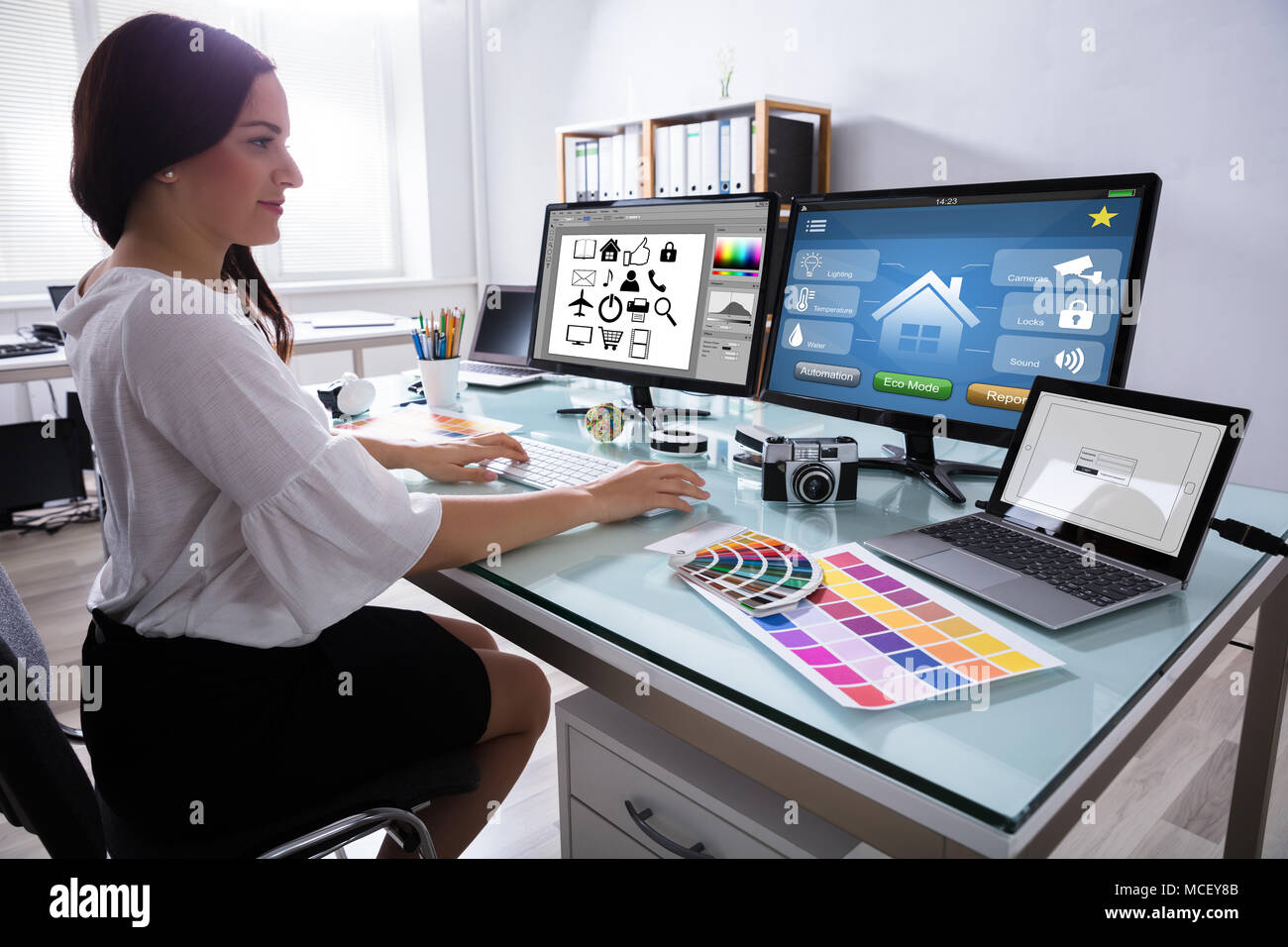 Close-up Of A Female Designer Working On Multiple Computer At Workplace Stock Photo