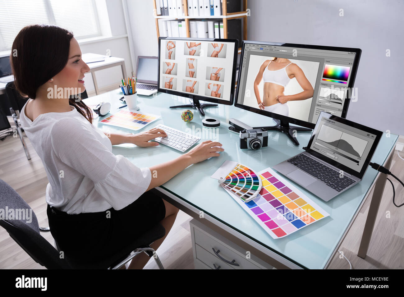 Happy Young Female Designer Working With Photographs On Multiple Computer At Workplace Stock Photo