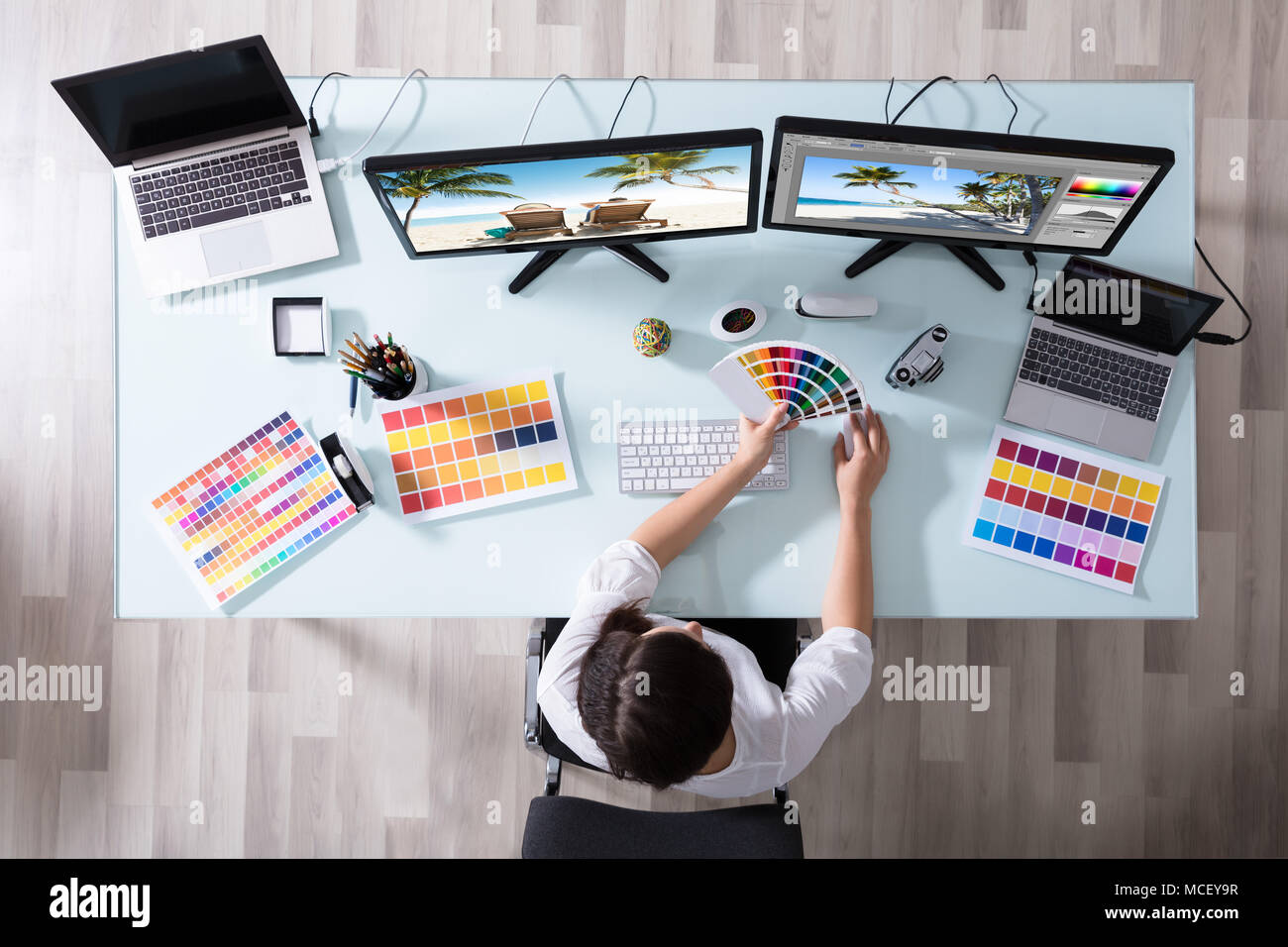 High Angle View Of A Female Designer Using Color Swatch While Working On Multiple Computer Stock Photo