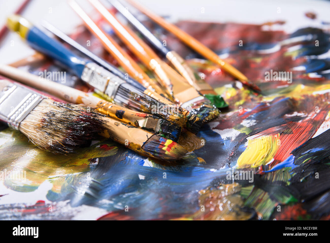Close-up Of Various Messy Paintbrushes With Multi Colored Paint On Canvas Paper - Stock Image