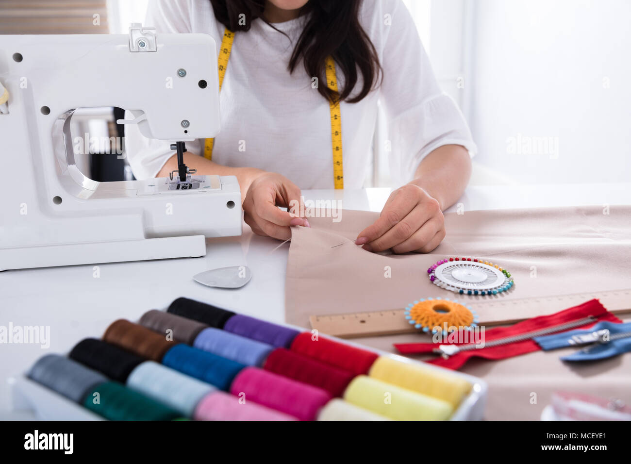 Close-up Of A Fashion Designer's Hand Measuring Fabric With Ruler In Studio - Stock Image