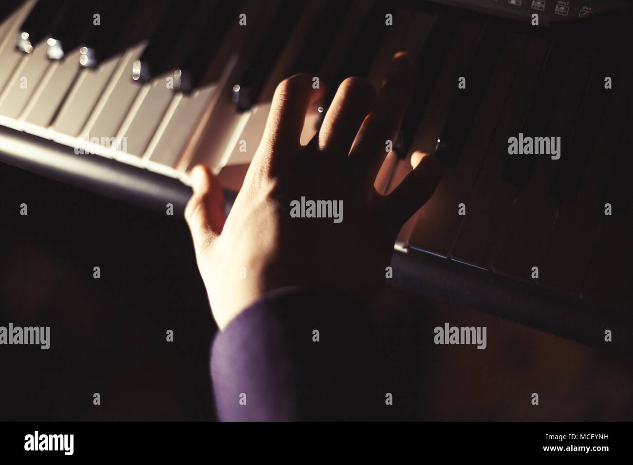 Playing on synthesizer keyboard - Stock Image