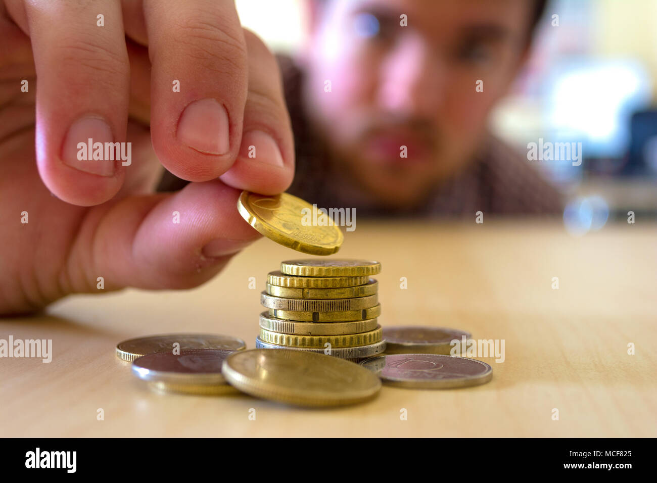 The coins are stacked. The men's hands are gently putting coin on top of the stack. Concept of saving money and growing financially. The new currency  - Stock Image