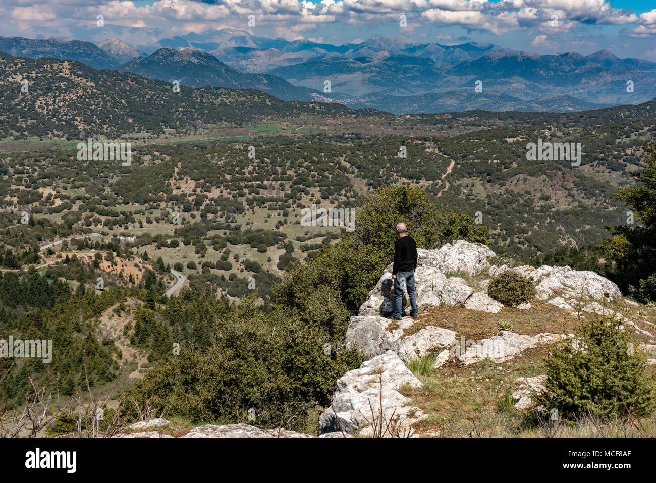 Man standing on rocks and enjoy the breathless view on Mainal mountain , Greece. - Stock Image
