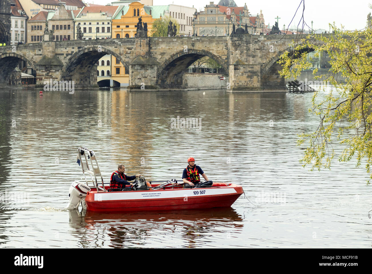 Prague - April 15: 2 firefighters sits in their boat and makes their training sail in the close neighborhood of Charles Bridge, on April 15, 2018 in P - Stock Image