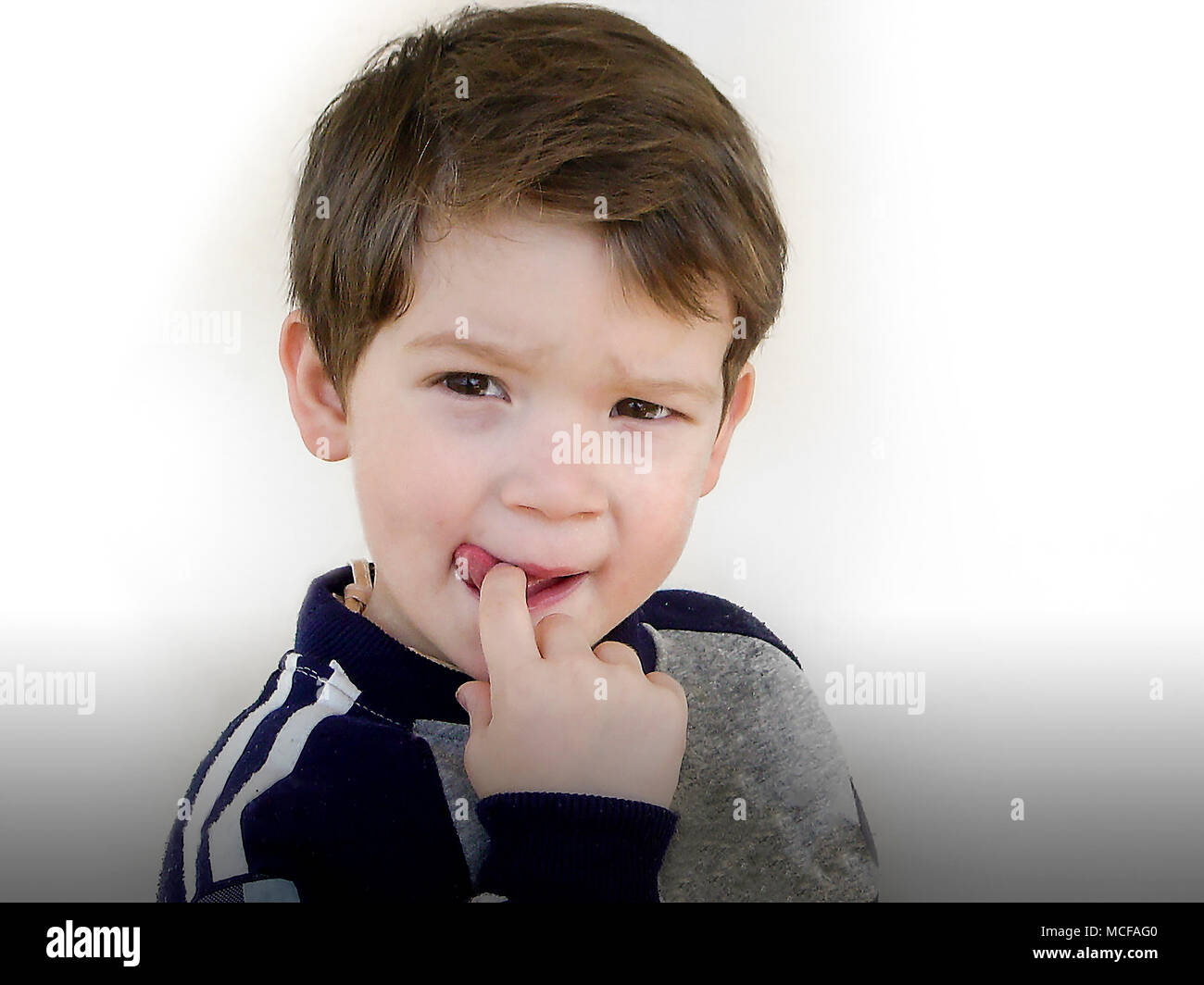 Portrait of an adorable little boy three years old who sucking on its finger, isolated on white background - Stock Image