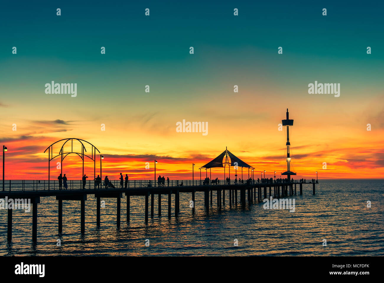 People walking along Brighton Jetty at sunset on summer evening - Stock Image