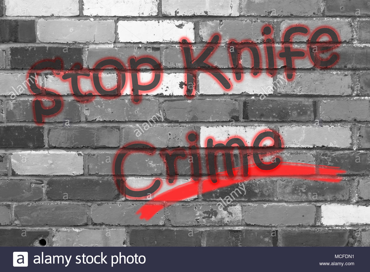 Looking at a black and white brickwall with the wording Stop Knife Crime. Dorset, England - Stock Image