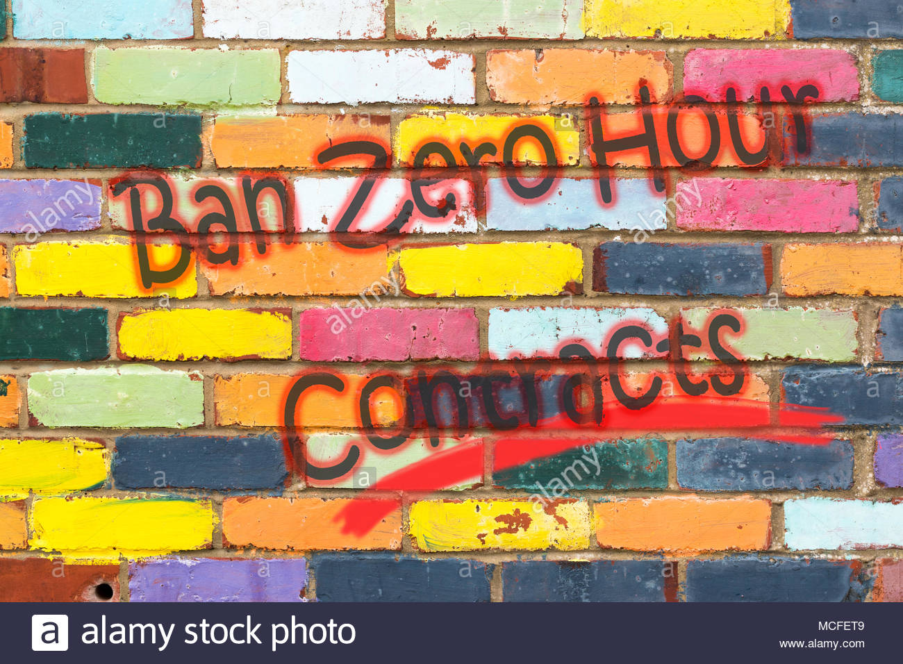 Looking at a very colourful brickwall with the wording Ban Zero Hour Contracts. Dorset, England - Stock Image