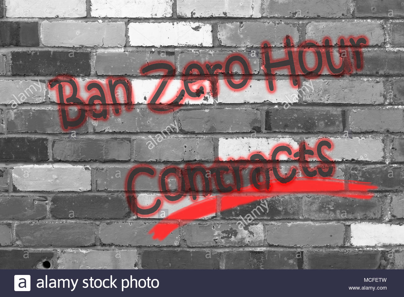 Looking at a black and white brickwall with the wording Ban Zero Hour Contracts. Dorset, England - Stock Image