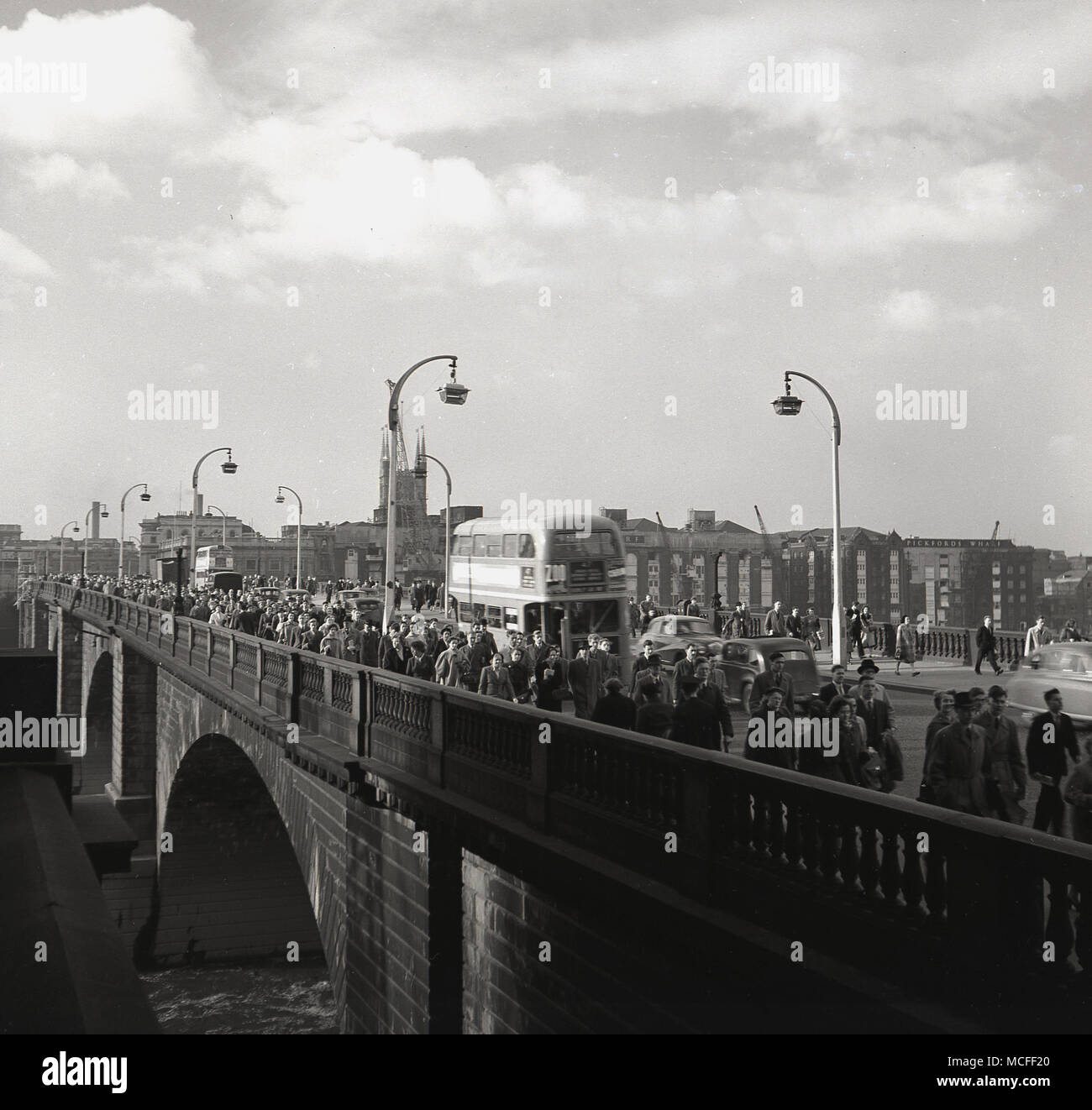 London, 1948, people crossing 'New' London bridge from Southwark on their way to work, London, England. Designed by John Rennie, it opened in 1831 and was composed of five stone arches, replacing the earlier Medieval bridge. The bridge became the busiest point in London and one of its most congested, with thousands of pedestrians and vehicles crossing it every hour. - Stock Image