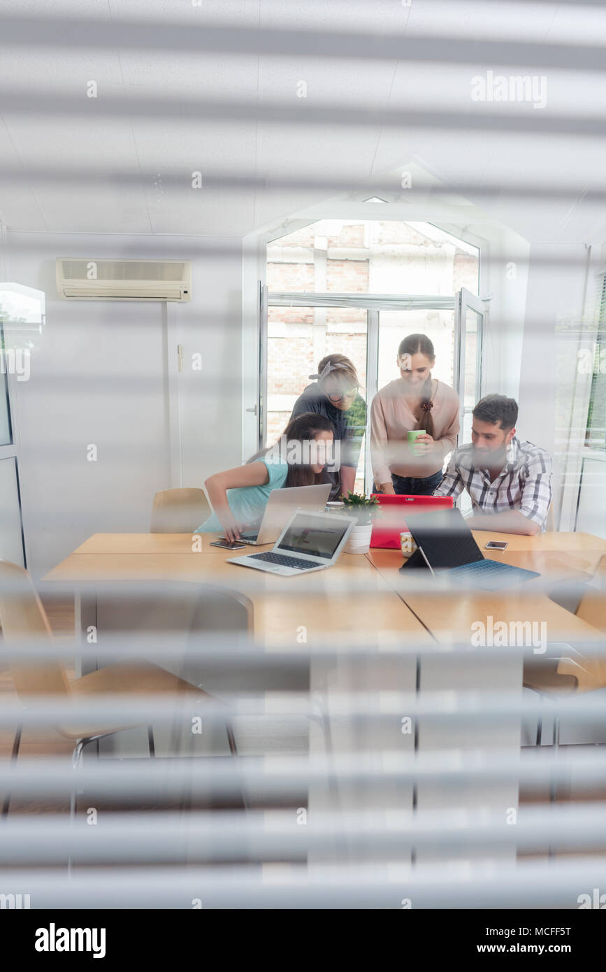 young independent workers sharing the facilities of a modern co-working space - Stock Image