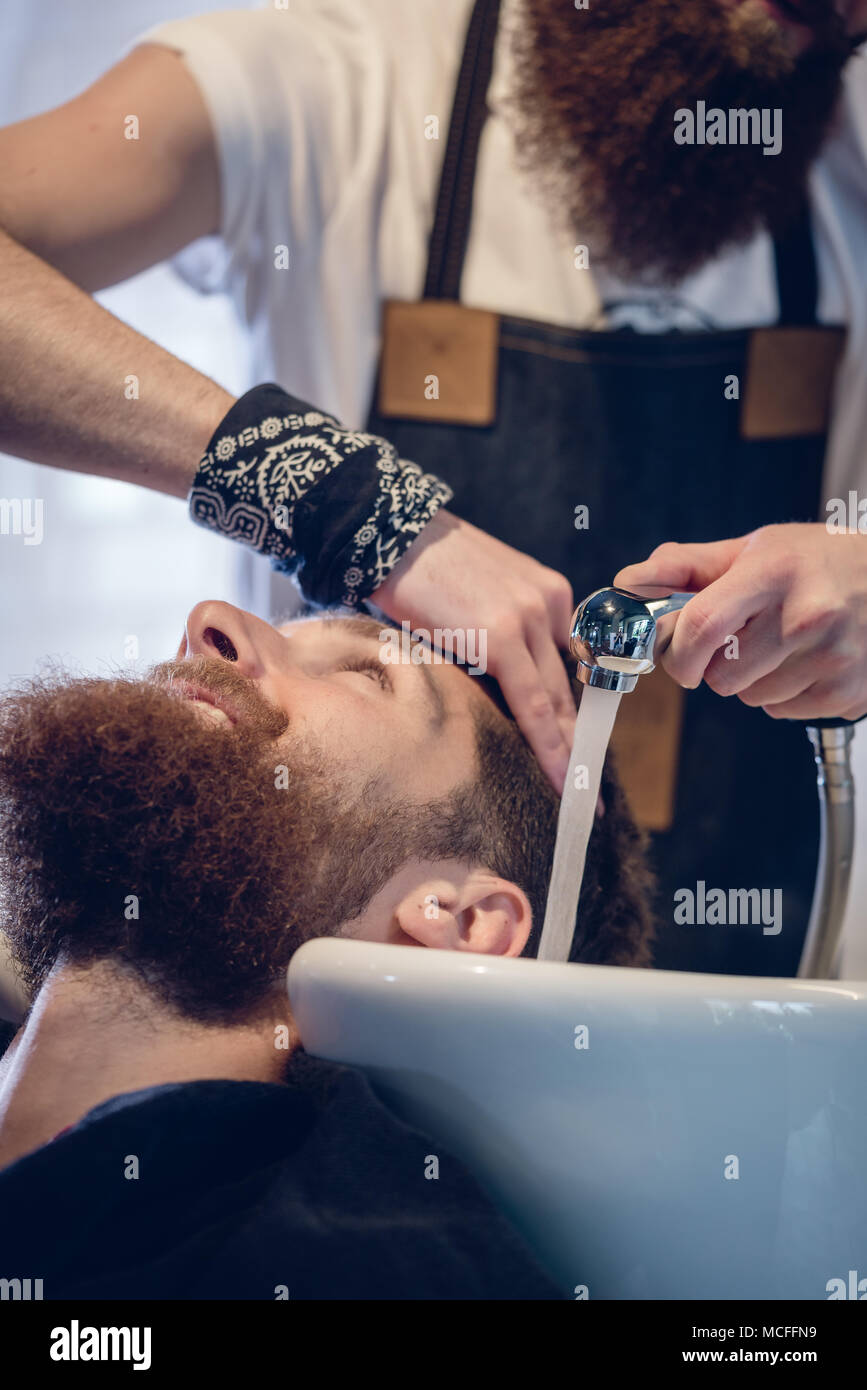 Close-up of the hands of a skilled hairdresser giving a hair wash to customer - Stock Image