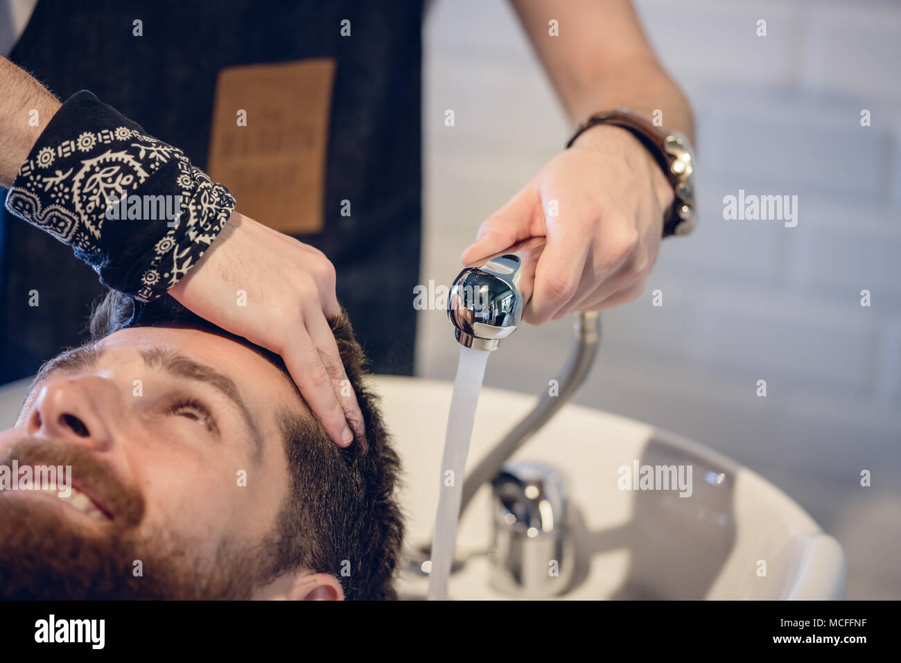 Close-up of the hands of a skilled hairdresser giving a hair wash - Stock Image
