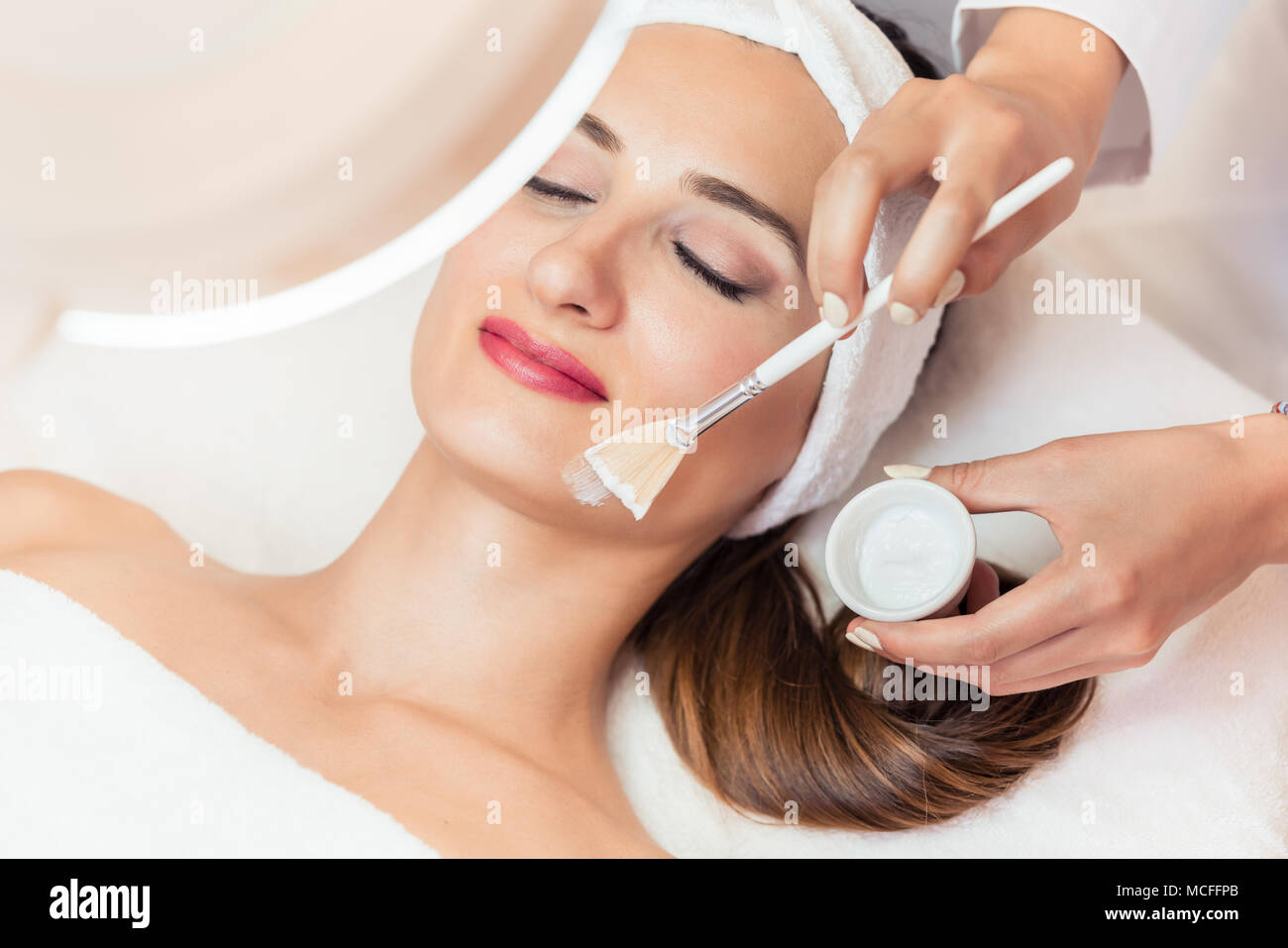 Close-up of a beautiful woman relaxing during facial treatment in beauty center Stock Photo