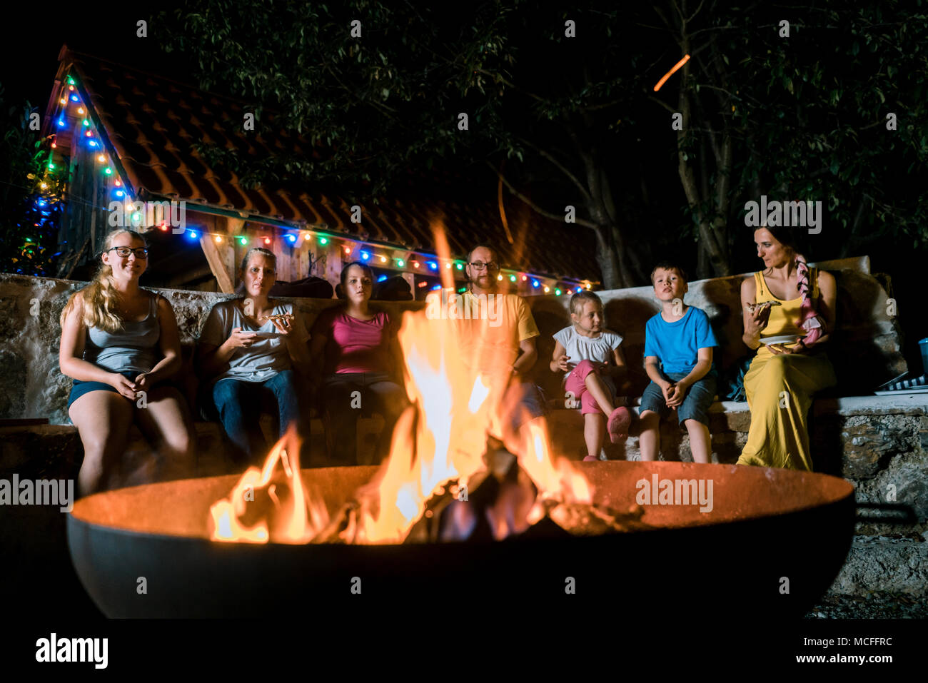 Family having a barbeque party sitting in front of fire - Stock Image