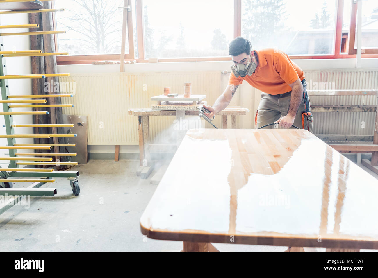 carpenter man spraying varnish on a table he works on - Stock Image