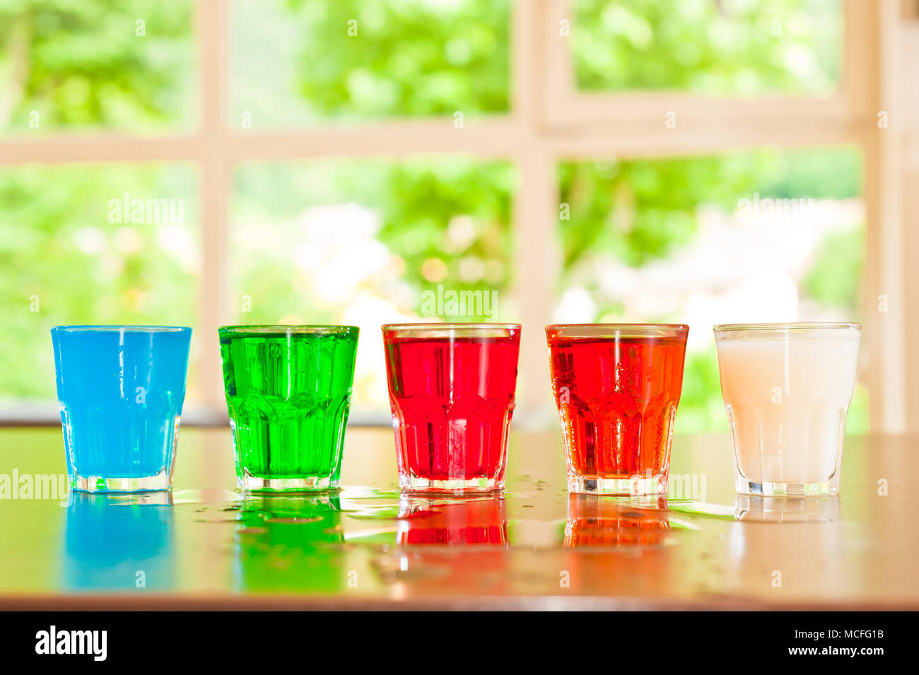 glass set with  colored cocktails - Stock Image
