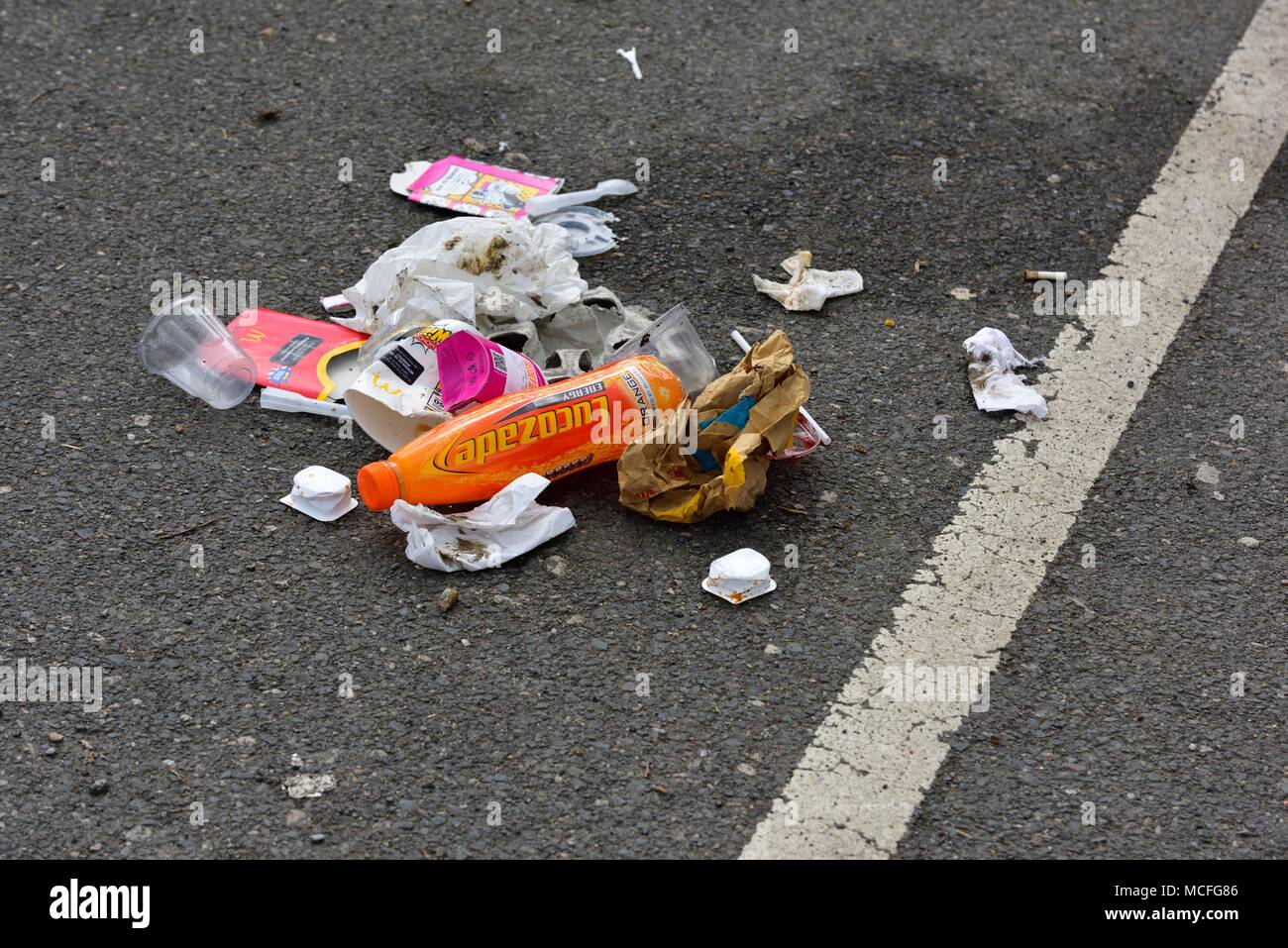 Rubbish dumped out of a car in a UK car parking space - Stock Image
