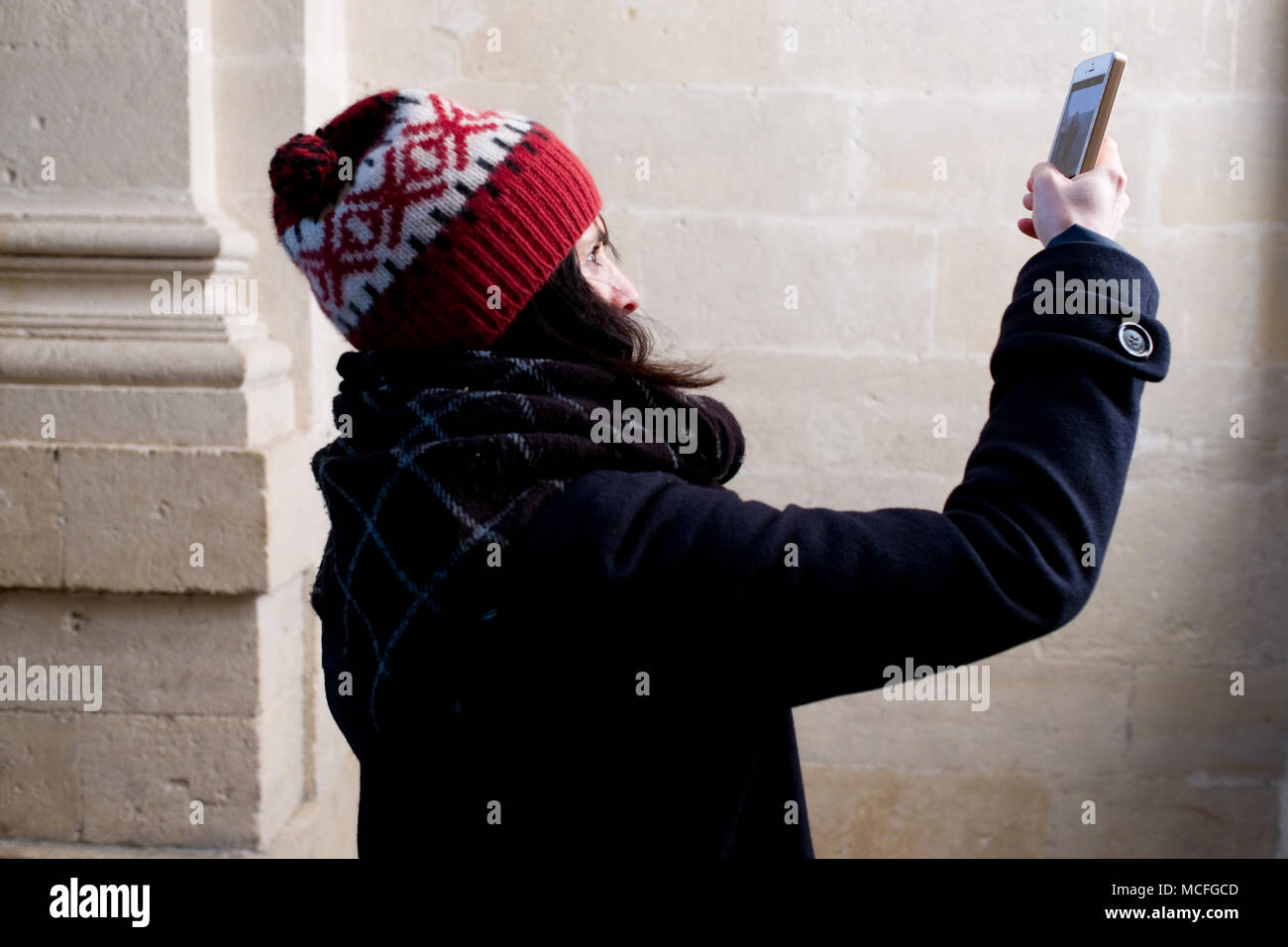 attractive middle-aged french woman with bobble hat takes a photo with her smartphone inside old church Stock Photo