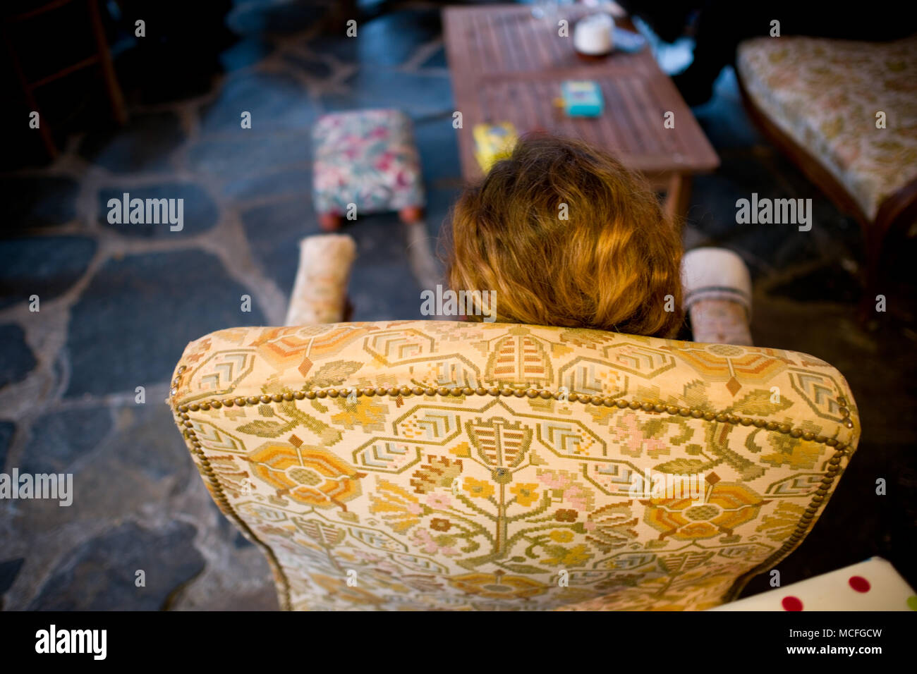 rear view shot looking down onto a woman sitting in an armchair on a stone floor in a cosy atmosphere - Stock Image