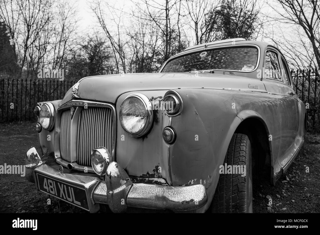 Black and white close up of a Rover P90 that has seen better times & is now an abandoned relic in retirement, alone in a deserted car park. - Stock Image