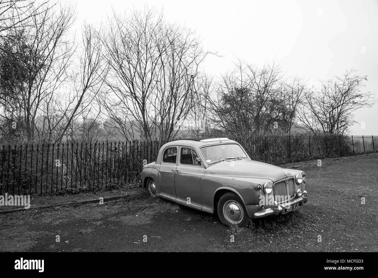 Black and white capture of a Rover P90 that has seen better times & is now an abandoned relic in retirement, parked alone in a deserted car park. - Stock Image