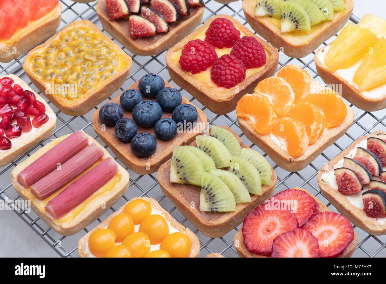 Colourful square fruit tarts on a wire cooling rack against a white background Stock Photo