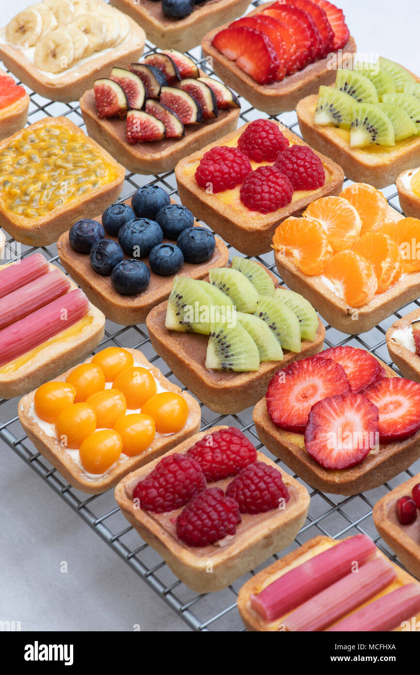 Colourful square fruit tarts on a wire cooling rack against a white background - Stock Image