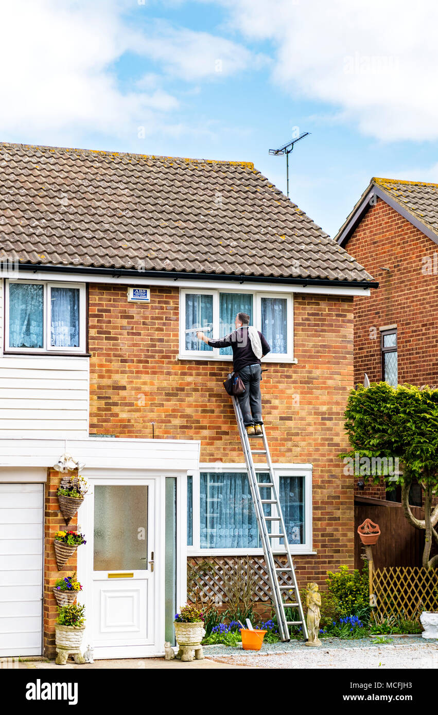 Man cleaning windows of a semi detached house - Stock Image