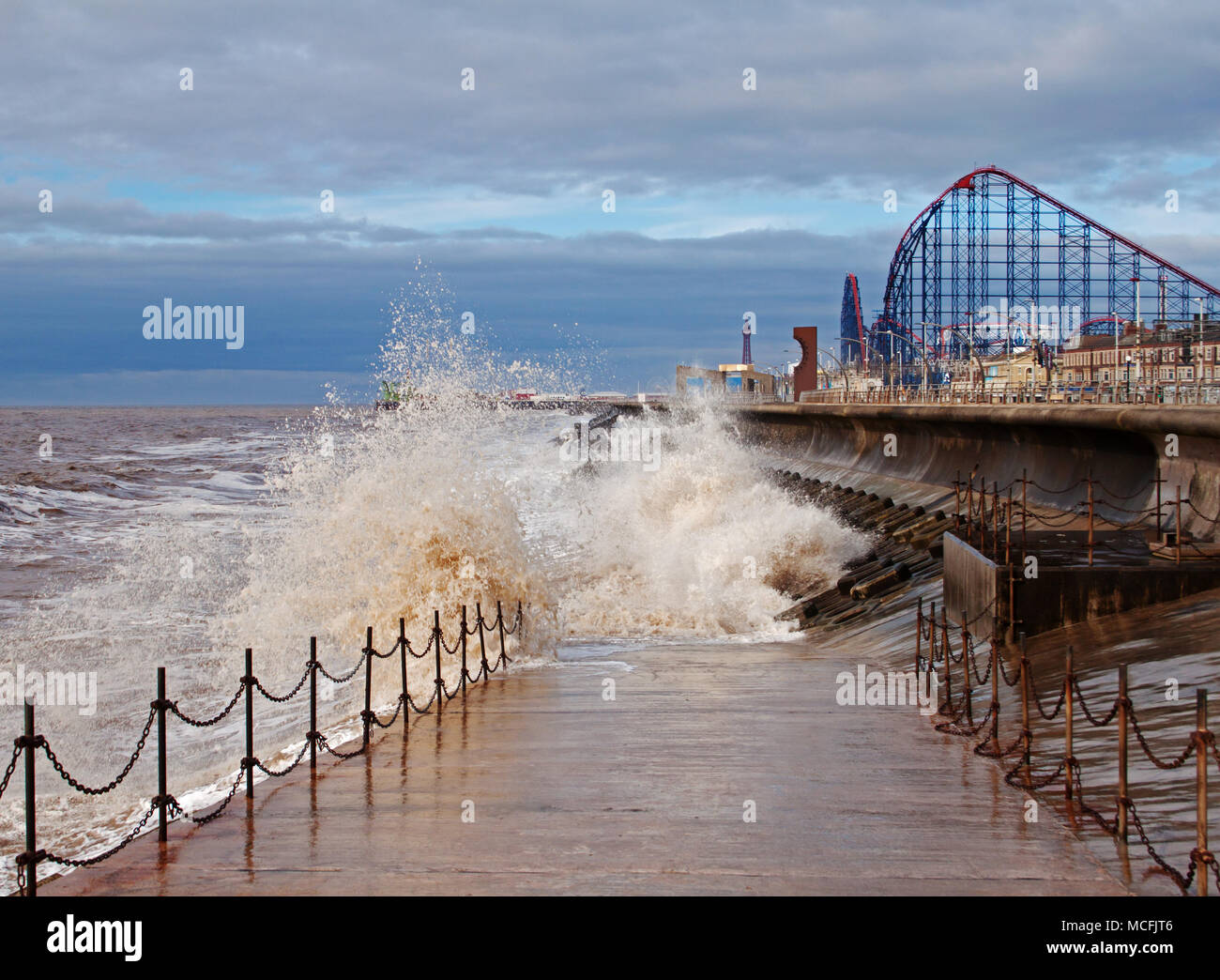 Waves splashing against Blackpool's sea defence, making a picturesque scene,  with the big one, Blackpool Pleasure Beach, in the background Stock Photo