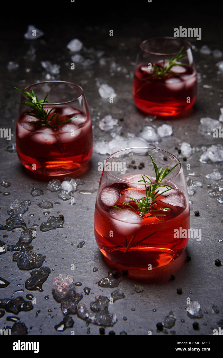 Pomegranate cocktail with ice and rosemary surrounded with crushed ice on the black concrete background. - Stock Image