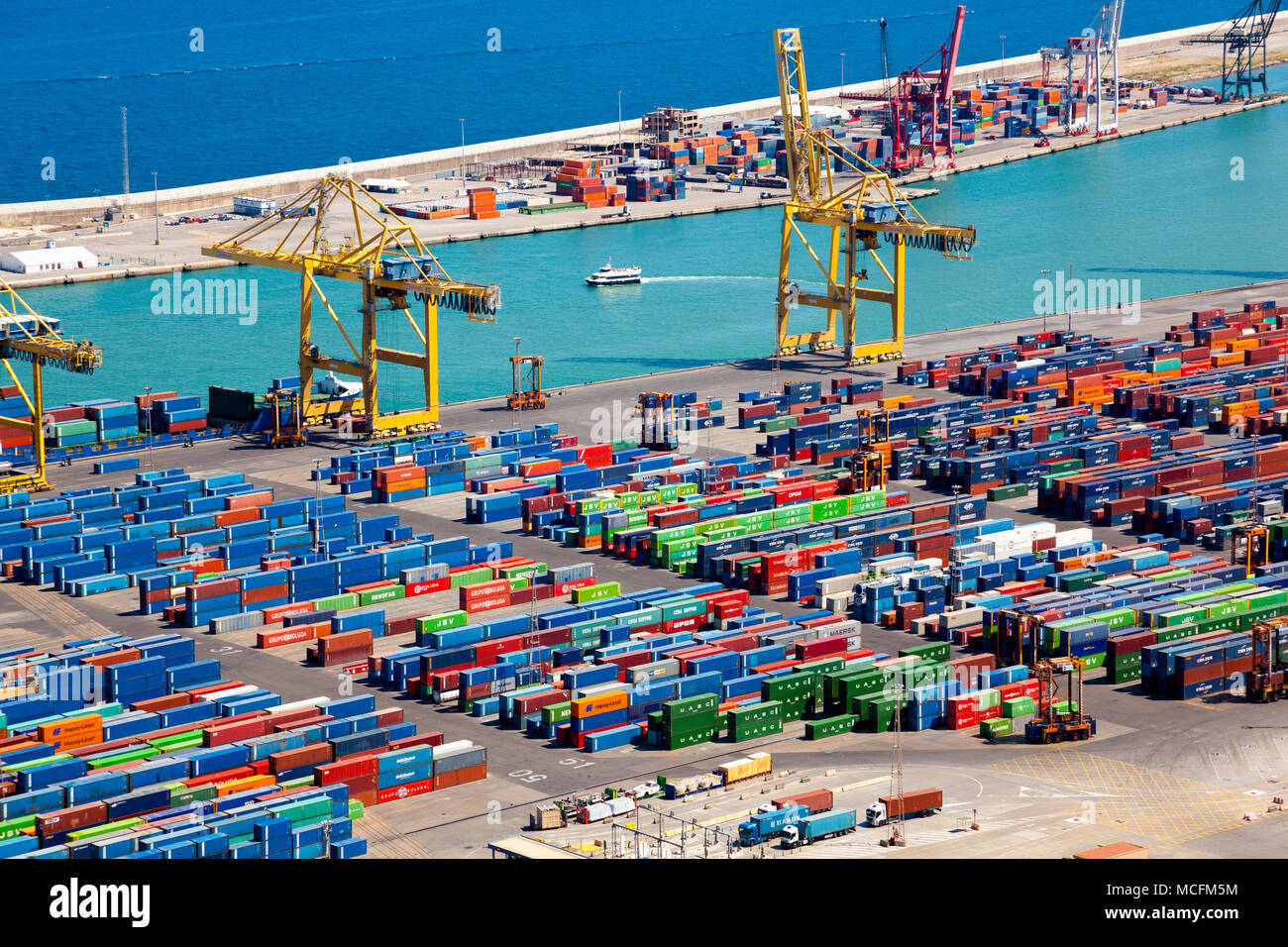 Yellow cranes and shipping containers at the Port of Barcelona, view from Montjuïc, Barcelona, Spain - Stock Image