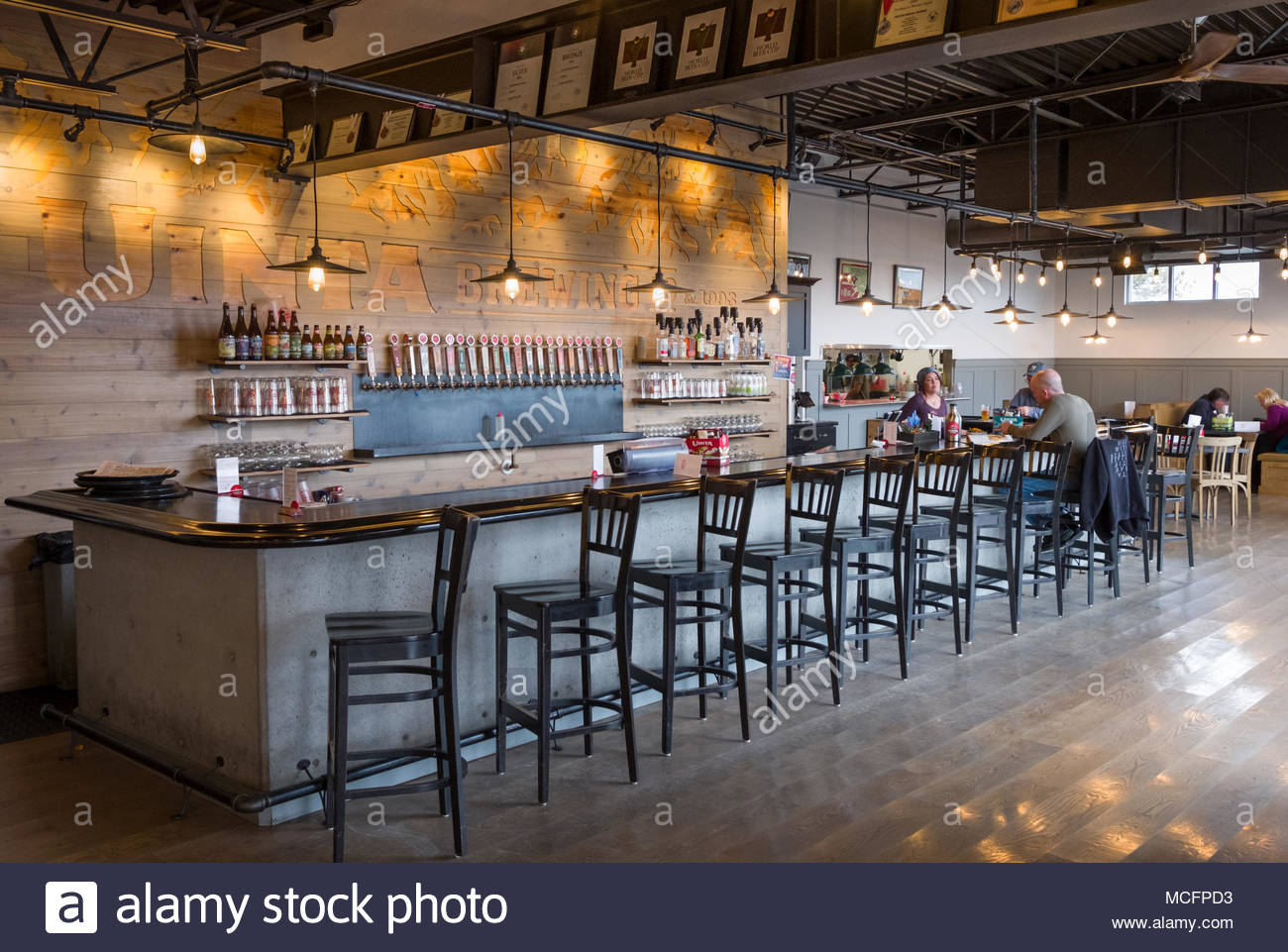 Woman Behind Counter Serving Drinks And Talking With Men Sitting At