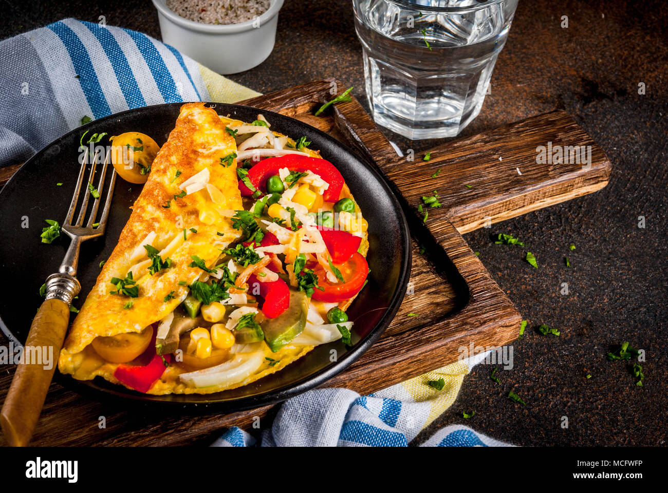 Healthy breakfast food, Stuffed egg omelette with vegetable, dark concrete background copy space - Stock Image