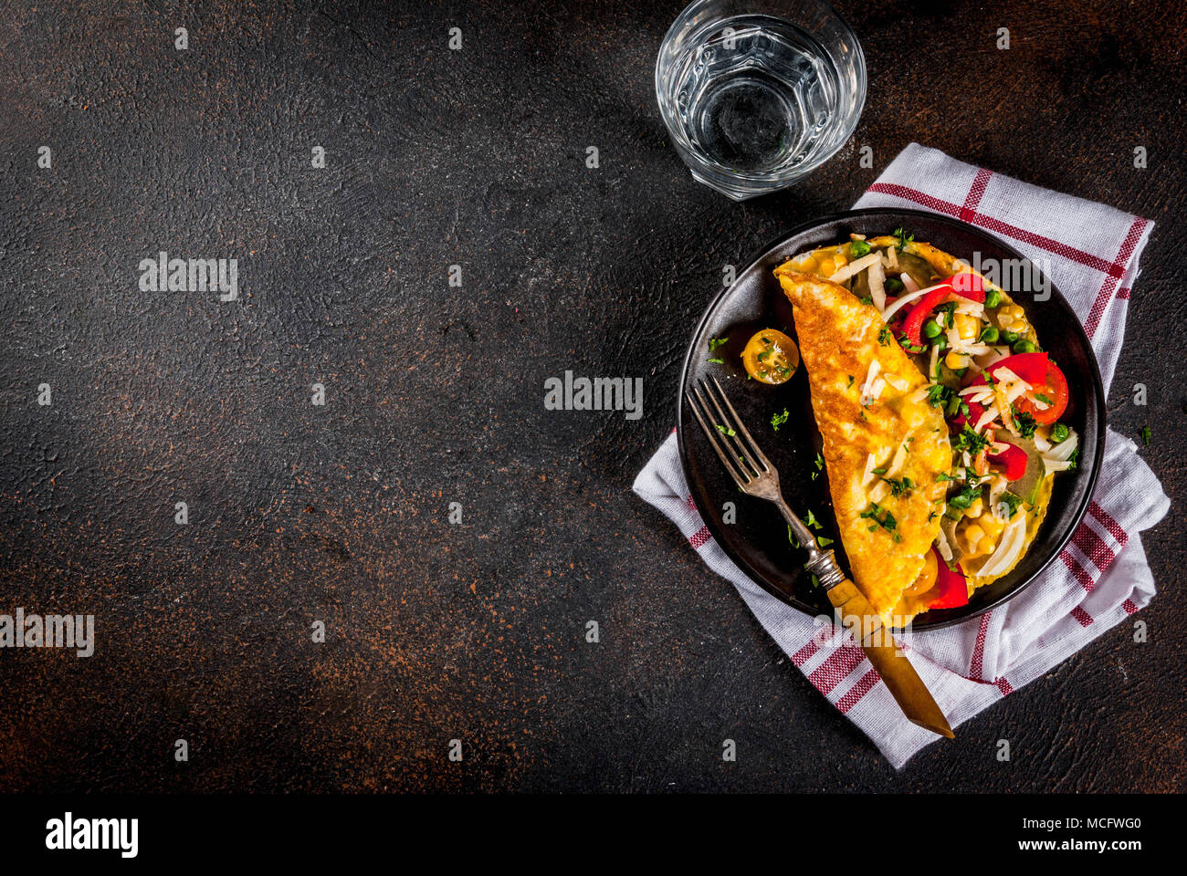 Healthy breakfast food, Stuffed egg omelette with vegetable, dark concrete background copy space top view - Stock Image