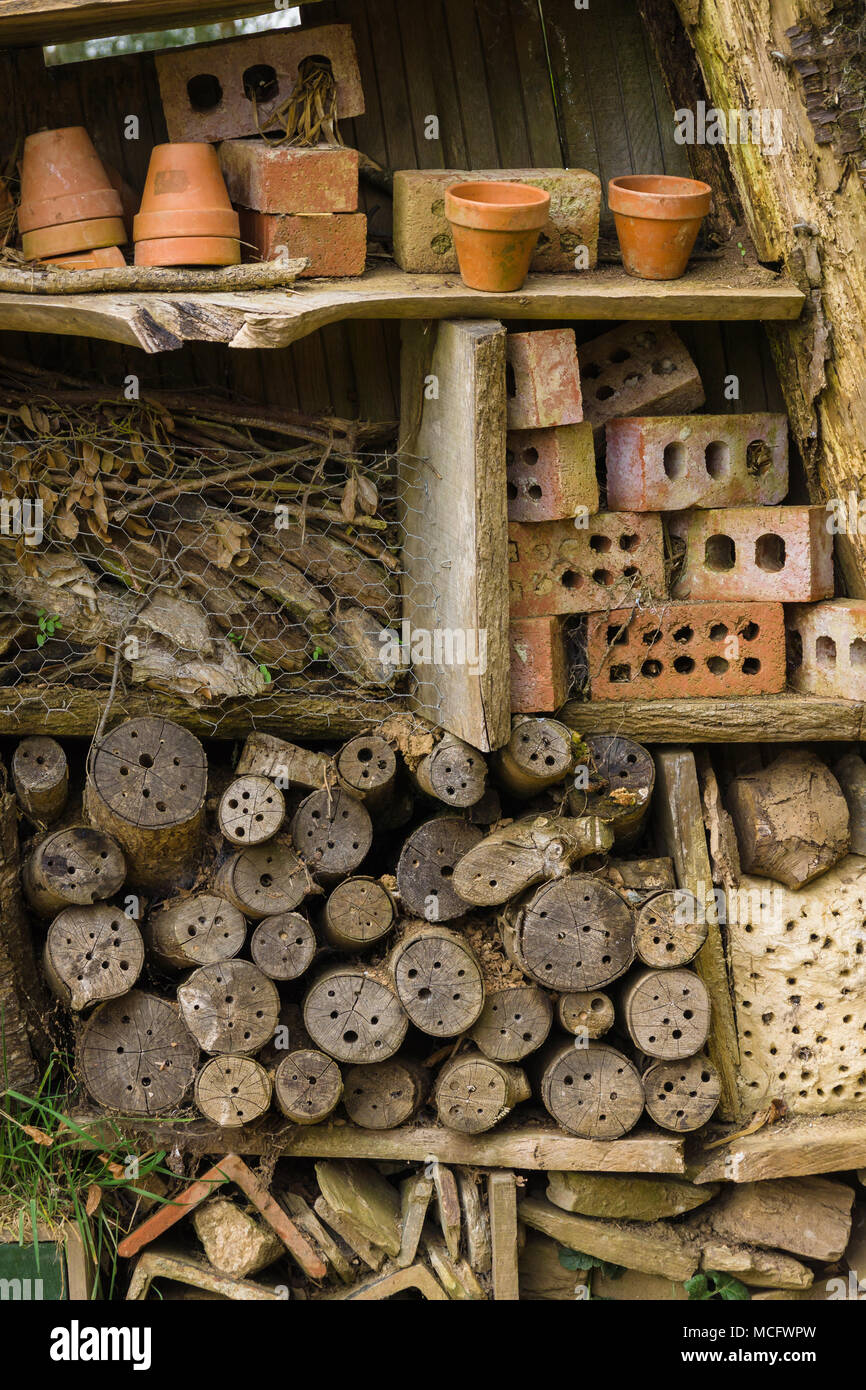Insect hotel or bug house made with old logs bricks and clay pots to provide shelter and a nesting or hibernation site for bees and insects Stock Photo