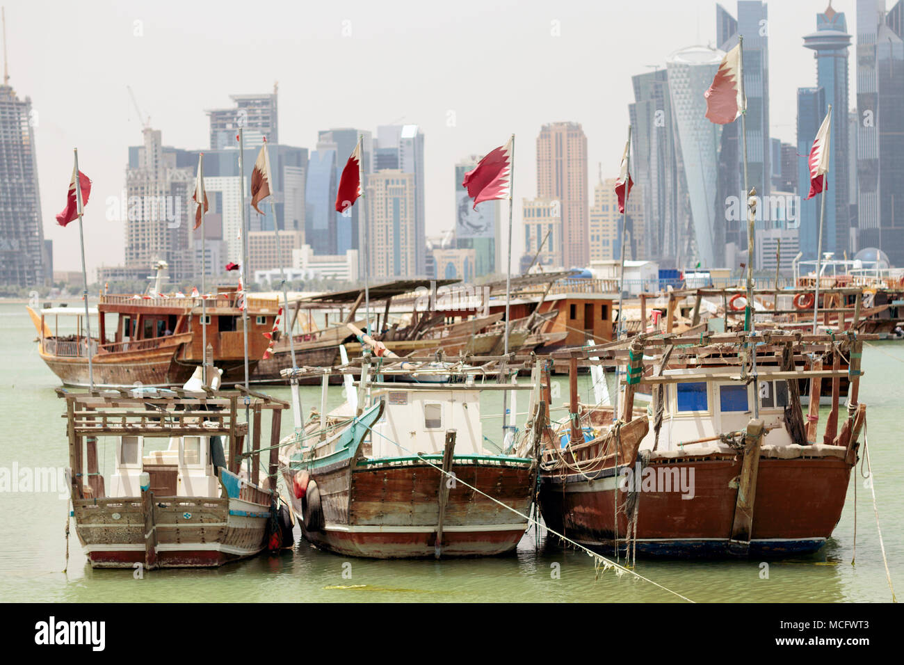 DOHA, QATAR - April 15, 2018: Small fishing boats flying qatari flags in the harbour with towers behind. Shows of loyalty have increased since Qatar w Stock Photo