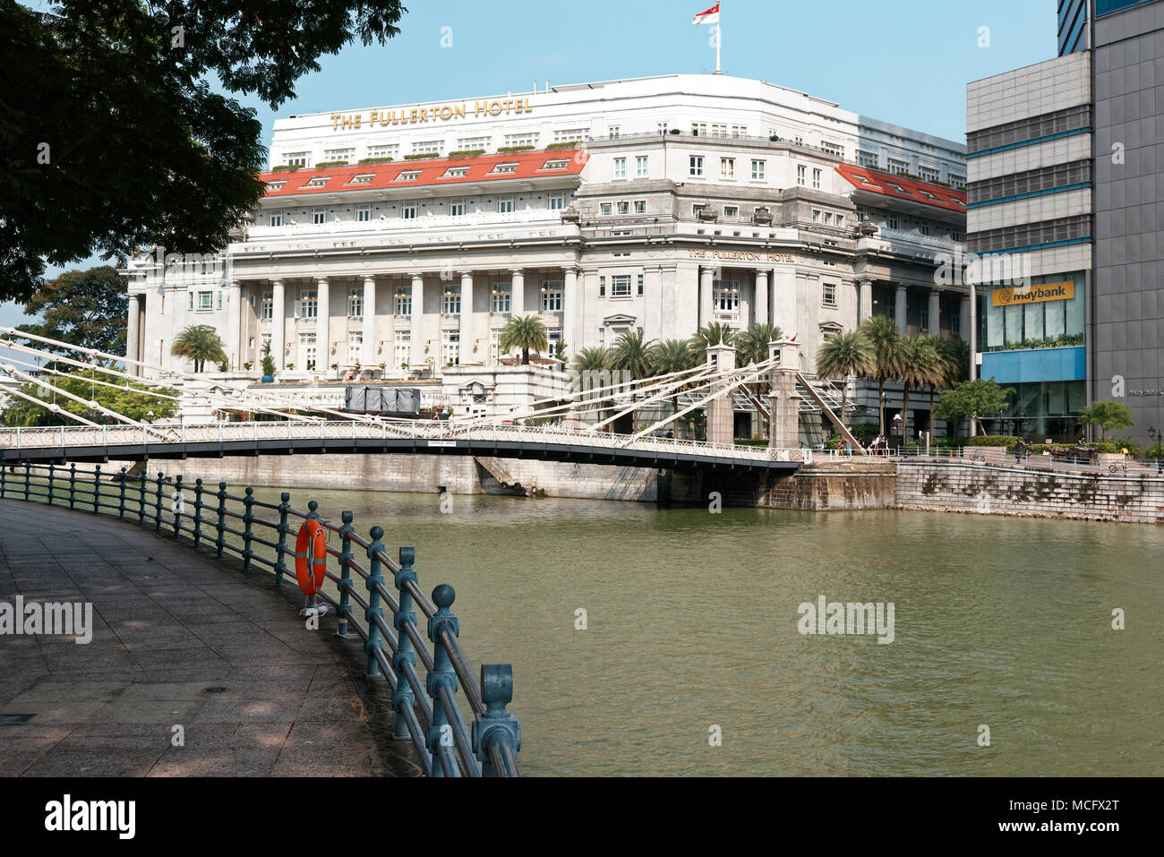 Cavenagh suspension bridge over the Singapore River and Fullerton hotel in the background. - Stock Image