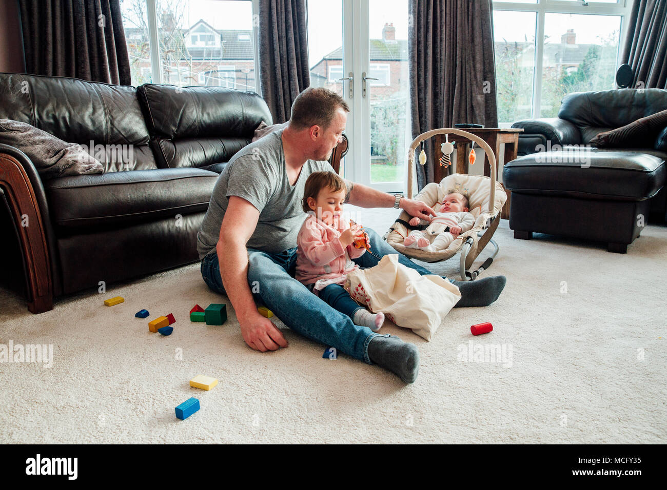 Stay at home father with his daughters at home. The eldest girl is sitting with her father playing with toy dinosaurs while the baby girl is in her ro - Stock Image
