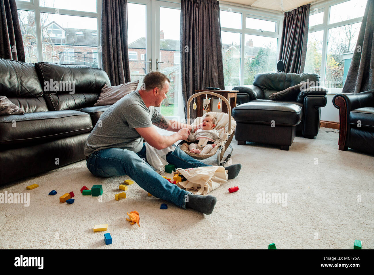 Stay at home father is relaxing in the living room with his baby daughter while she is in her baby bouncer. - Stock Image