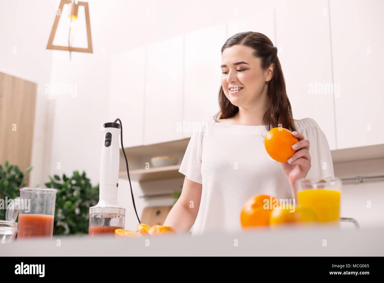 Glad jolly woman squeezing orange fresh - Stock Image